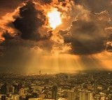 Rays of light shining through dark clouds in the Bangkok city