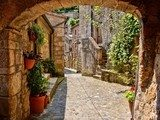 Arched cobblestone street in a Tuscan village, Italy