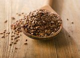Flax seeds heap on a wooden spoon