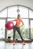 Woman holding fitball in a fitness studio