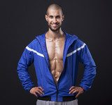 Smiling athletic man showing six pack abs on black background