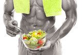 Bodybuilder holding a bowl of fresh salad, isolated on white bac