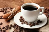 Coffee beans and cup of coffee on table on brown background