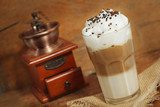 latte macchiato with cocoa powder and coffee beans on wooden tab
