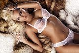 Fashionable photo of young blonde woman wearing white lingerie