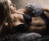 A young and sexy blond woman in erotic lingerie and fur