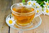Herbal chamomile tea in a glass cup on a board