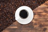 Coffee cup and beans on a rustic background