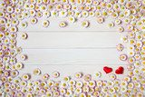 Wooden light background with daisies and red hearts