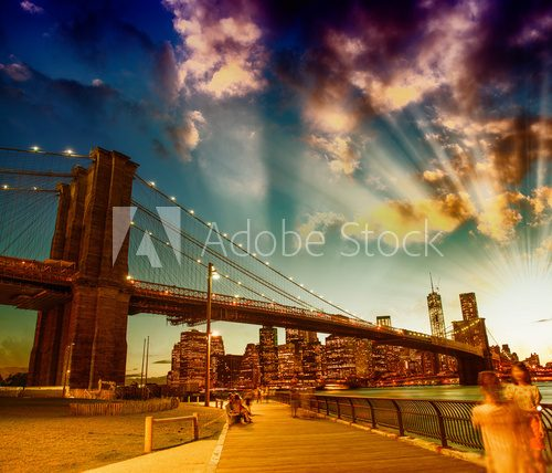 Relaxing in Brooklyn Bridge Park at summer sunset. Beautiful New
